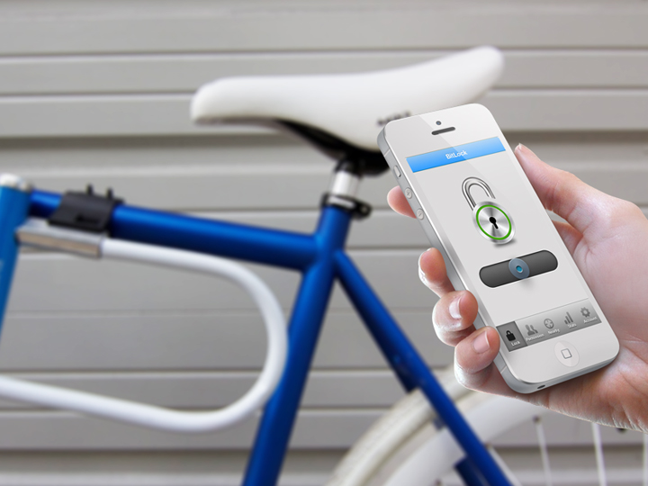 Bitlock hand-held device in person's hand with bike in background