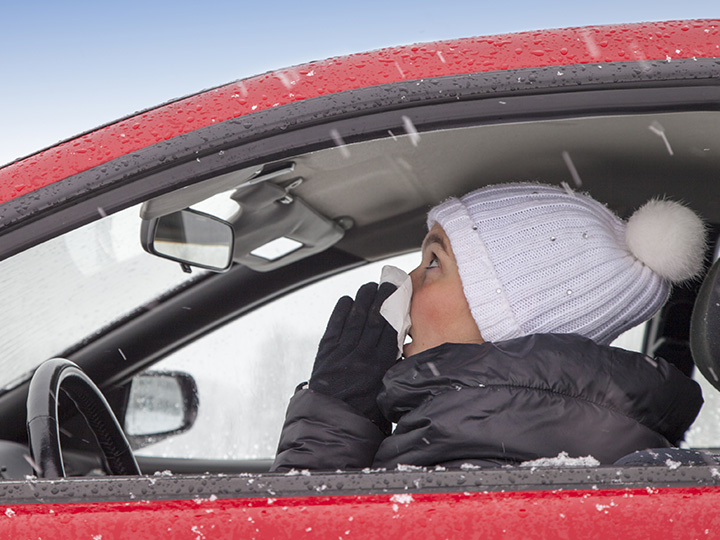 person in winter clothes sitting in car and blowing nose