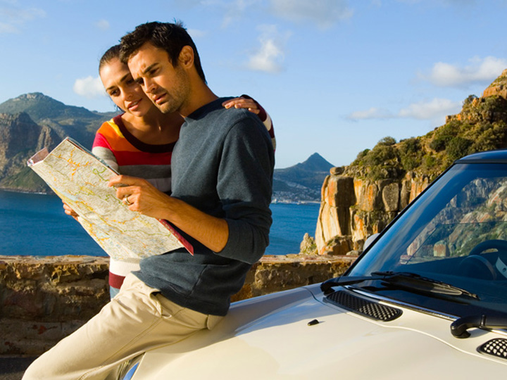 two people looking at a map while sitting on a car hood