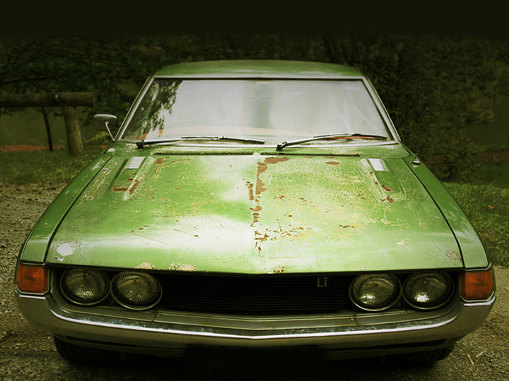 old, scraped up, green car