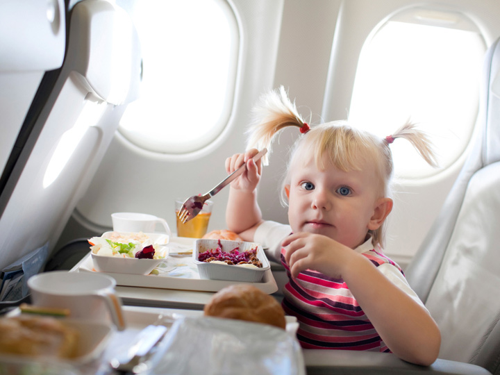 kid eating food on an airplane