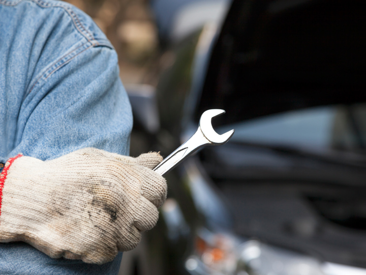 hand holding a wrench with car in background with hood popped