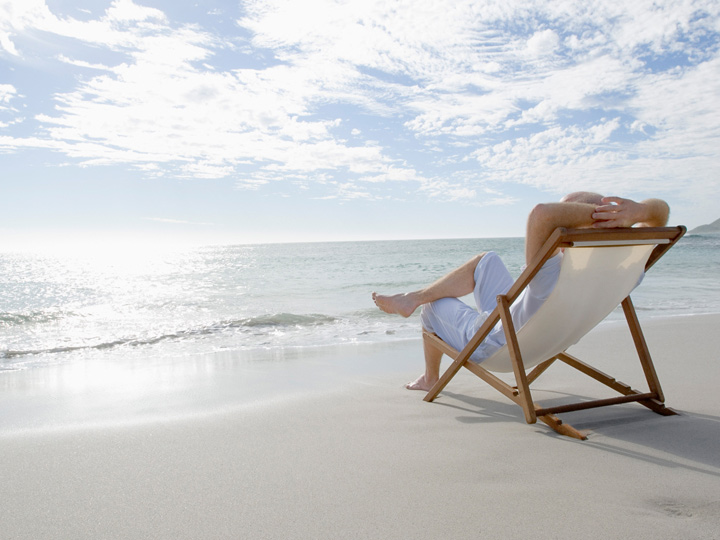 person relaxing in a chair on the beach
