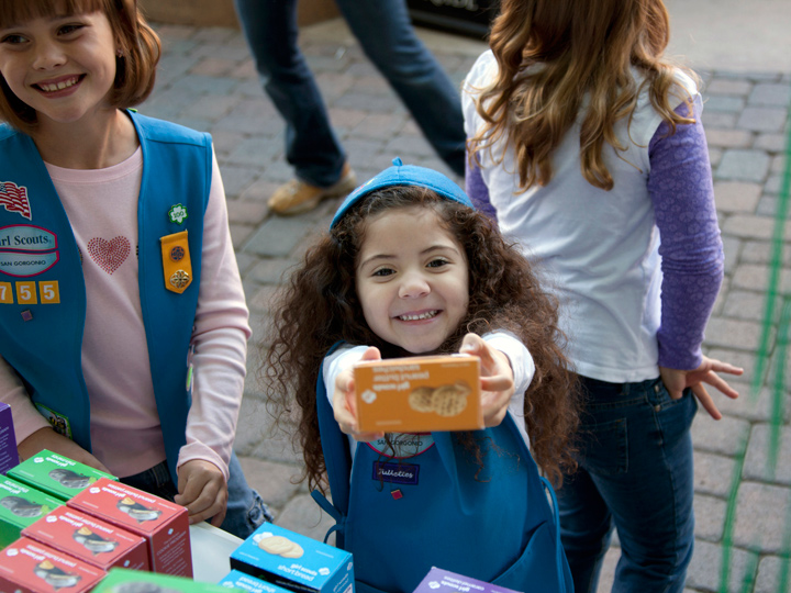 small girl holding box of girl scout cookies out to camera