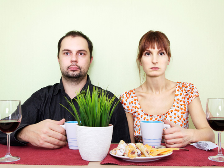 two people drinking coffee and looking at the camera