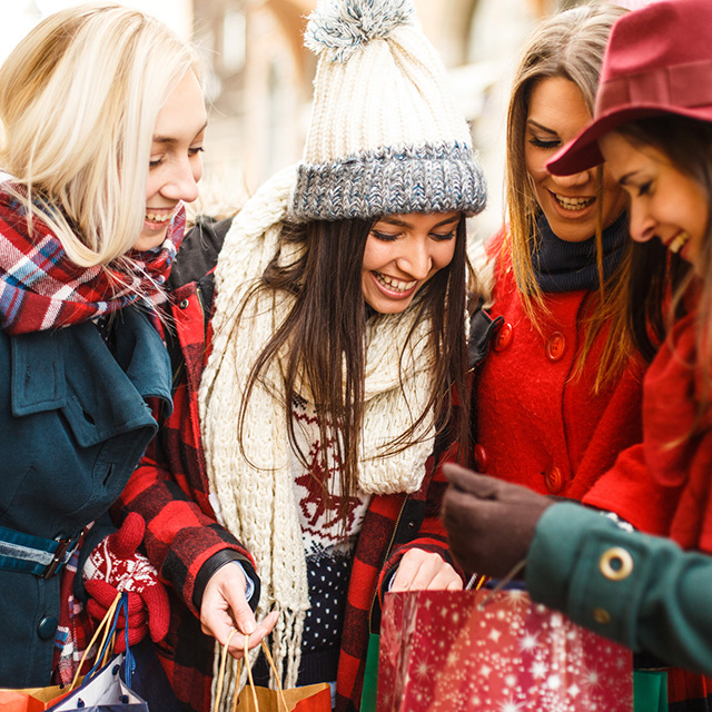 Four women in winter clothes, smiling and looking into a gift bag