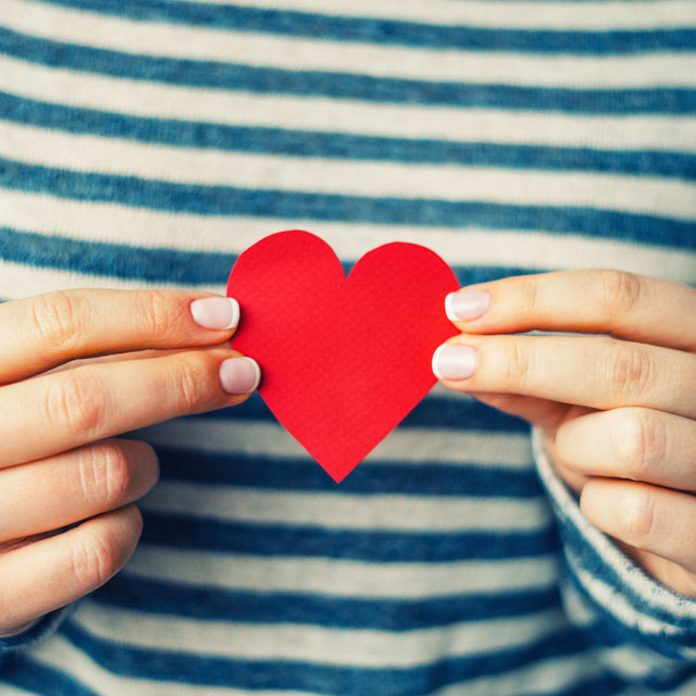 a person holding a small cutout heart with both hands