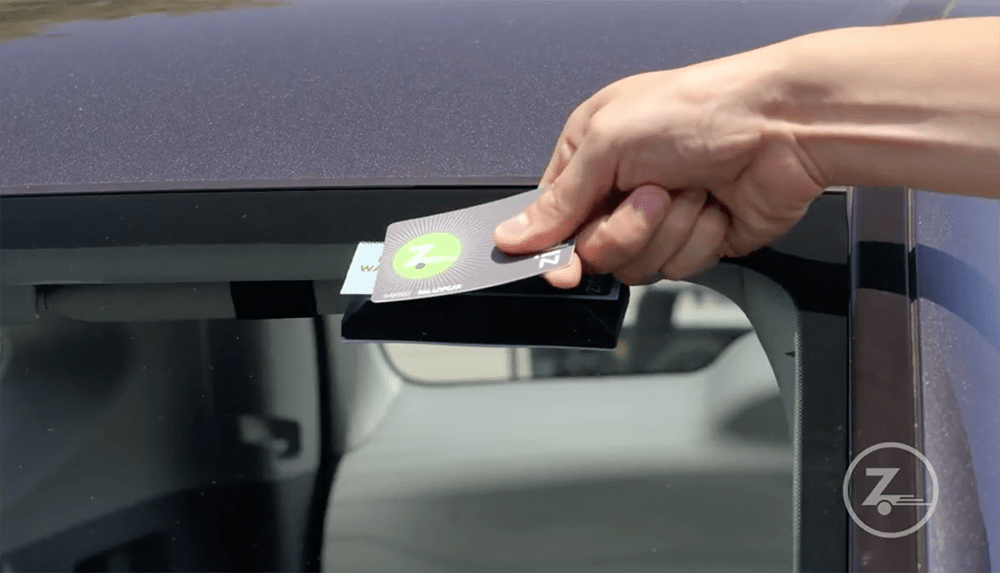 photo of a hand holding a Zipcard up to a windshield sensor
