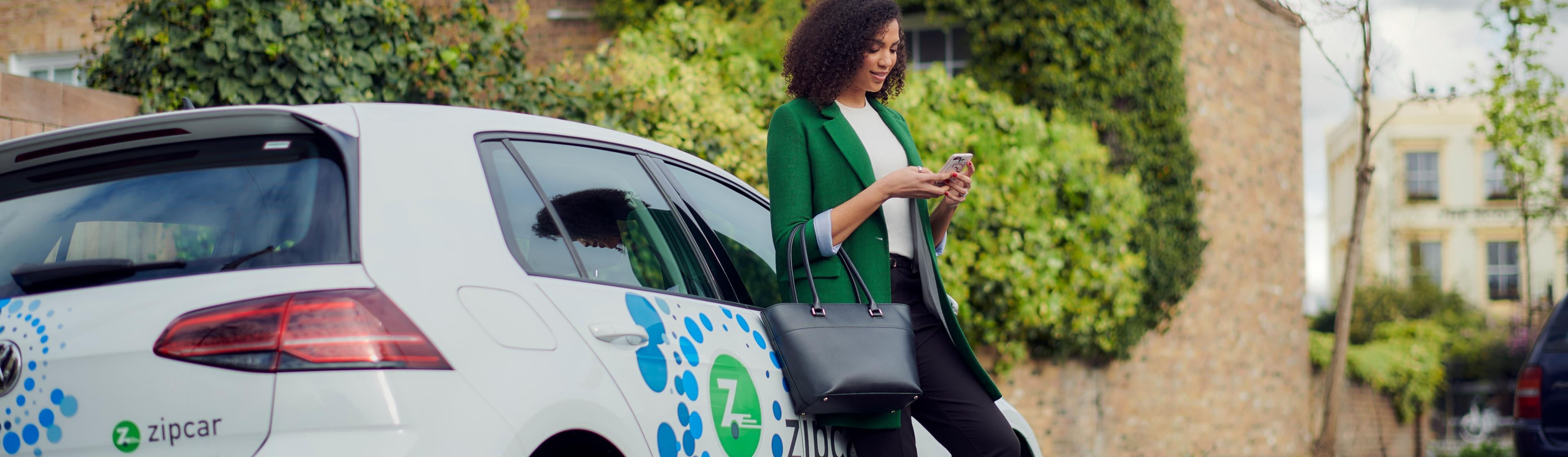 woman leaning on zipcar rental car