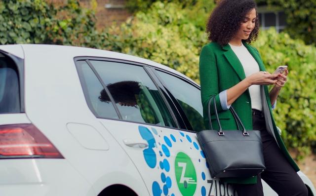 woman leaming on an electric zipcar flex
