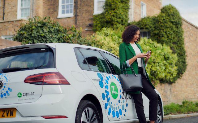 women leaning on a zipcar rental car