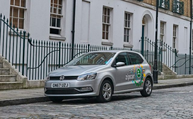 zipcar parked on a cobbled london street