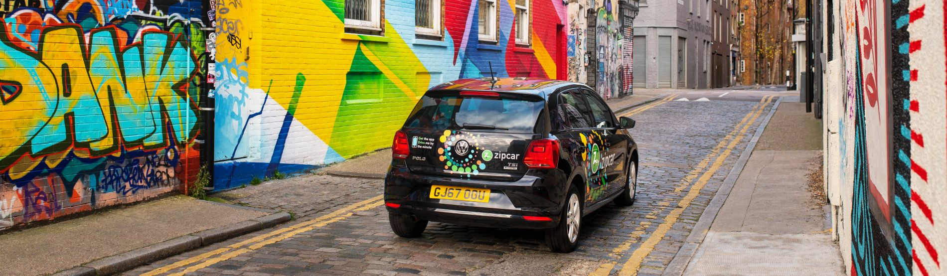 zipcar on a graffiti covered street in east london