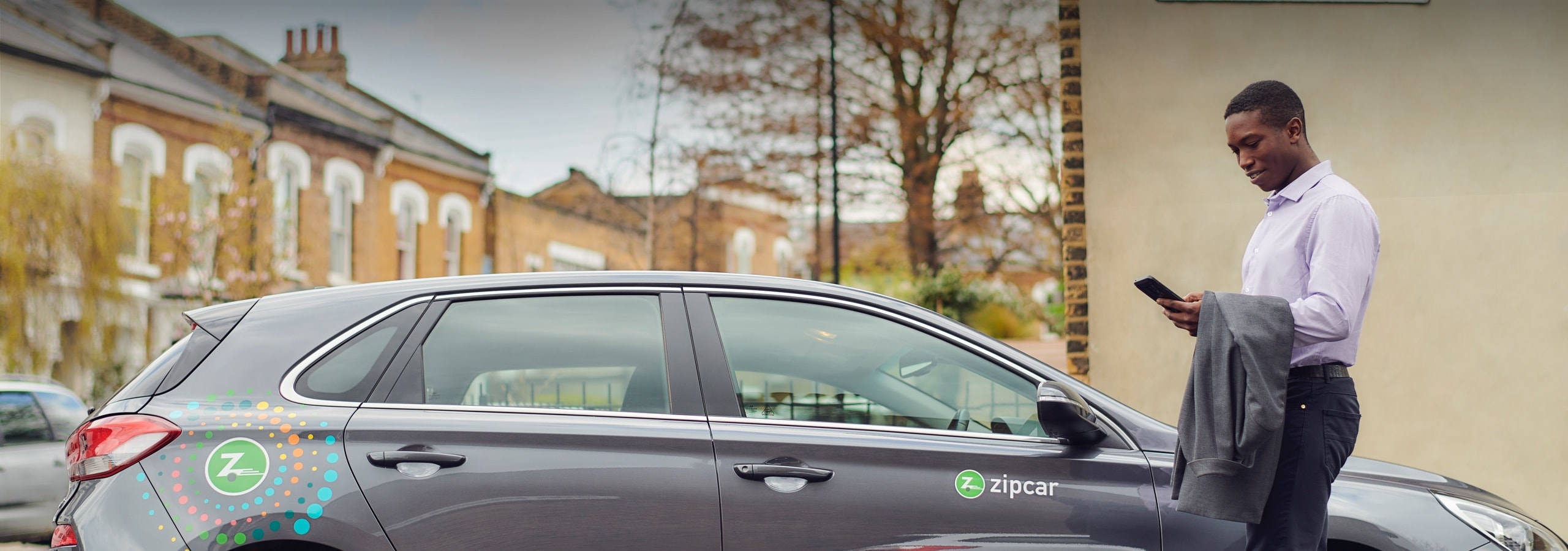man in a suit holding a cell phone on the size of a zipcar