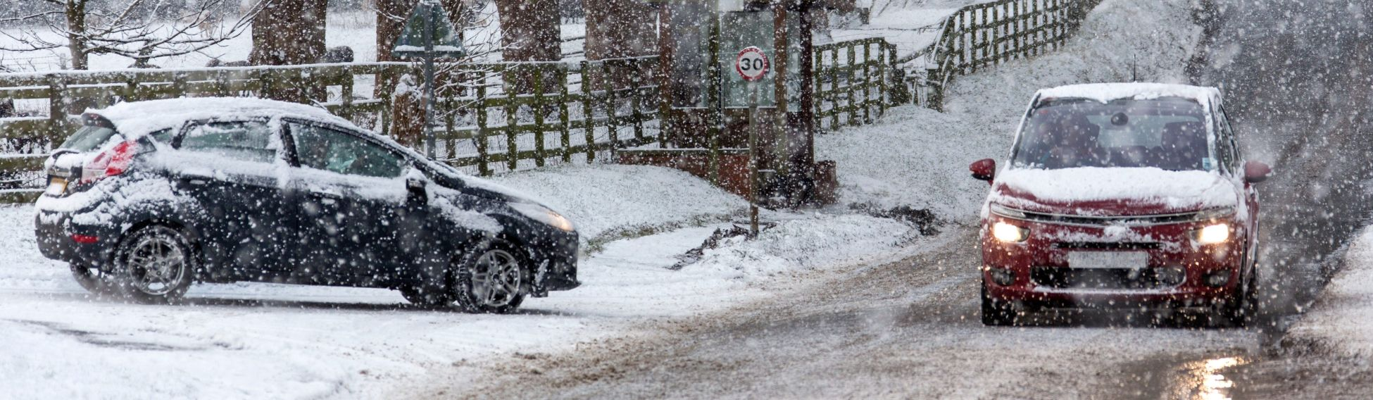 2 cars driving in the snow