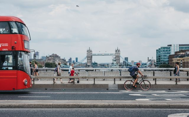 Cyclist, pedestrians and double decker bus on London Bridge
