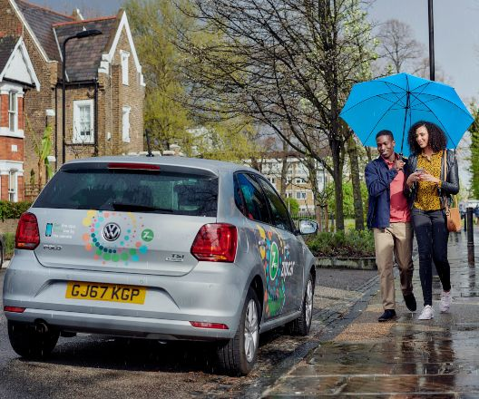 a couple escaping the rain by renting a zipcar flex to get them home