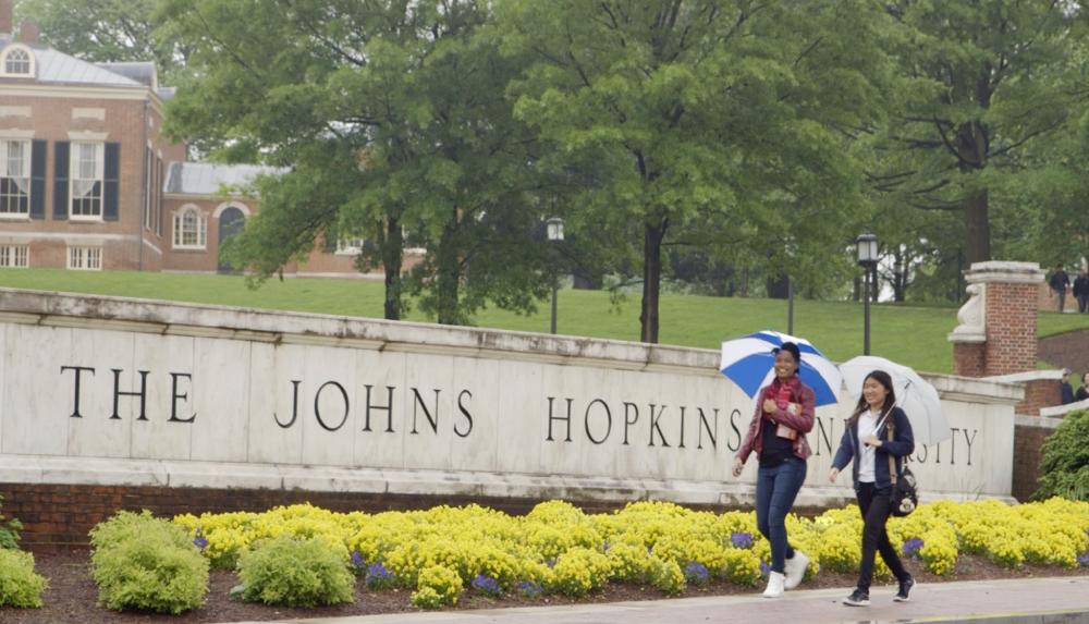 Two women walking with umbrellas infront of Jonhs Hopkins