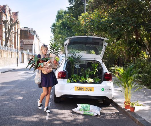 woman loading plants into the back of a zipcar flex