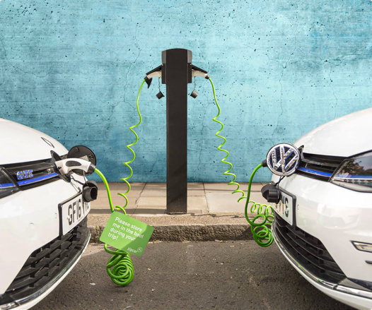 two electrical cars plugged in and charging