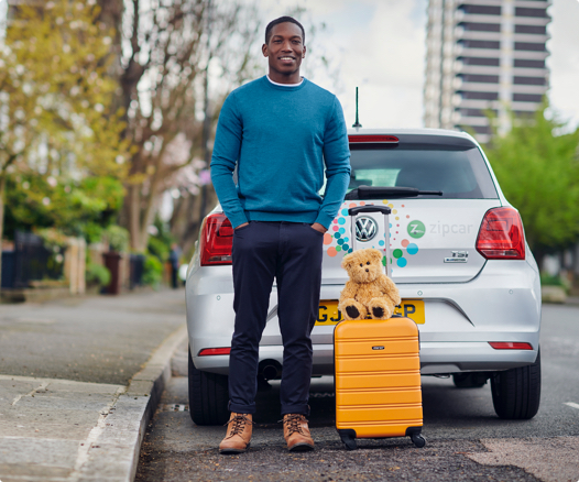 smiling man standing behind car with rolling suitcase
