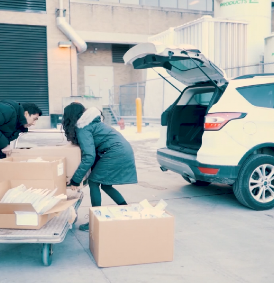 Students Loading boxes in the back of a car