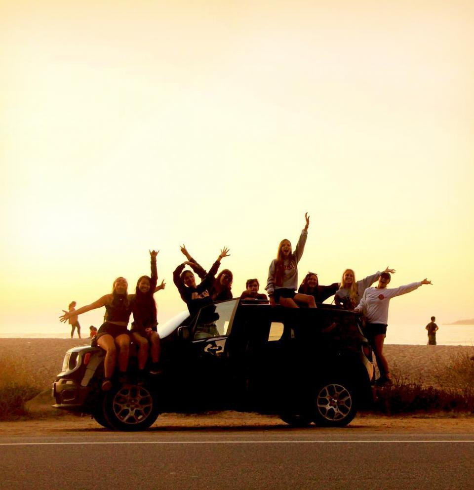 Silhouette of a group of people leaning out of a car