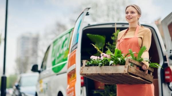 woman standing next to a Zipvan holding plants