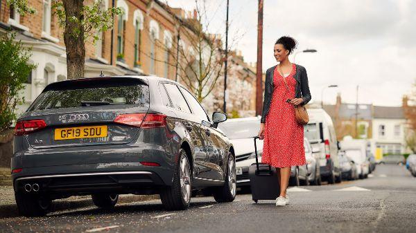 woman walking up to a zipcar car sharing car to rent it