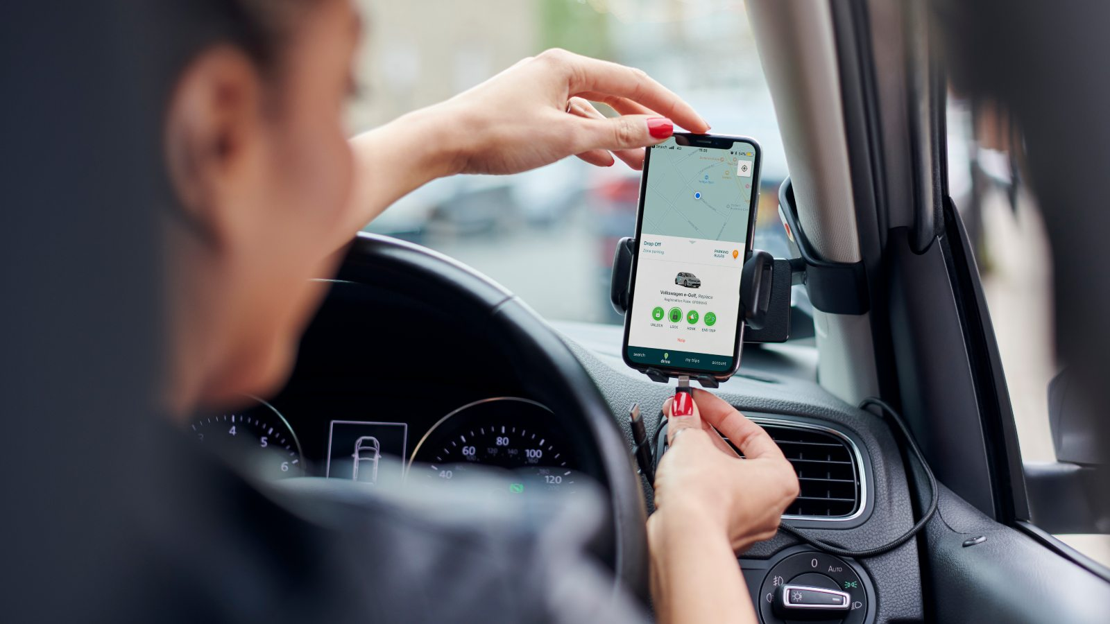 plugging in phone at the wheel of a zipcar