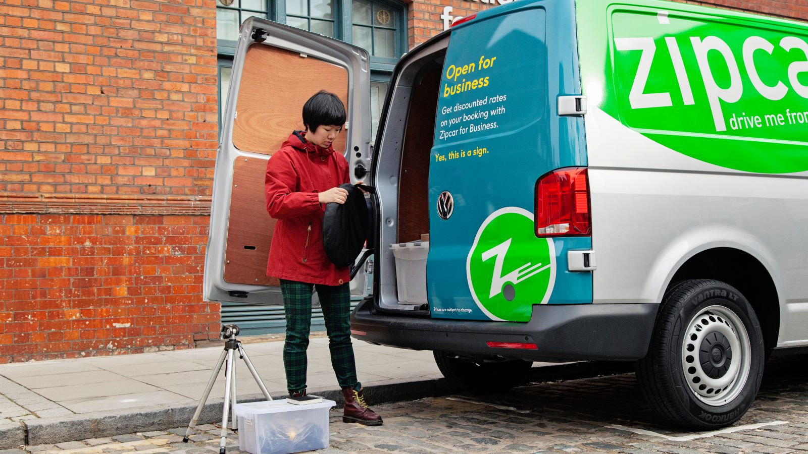 woman using a Zipcar van for a photo shoot. Loading a tripod into a van