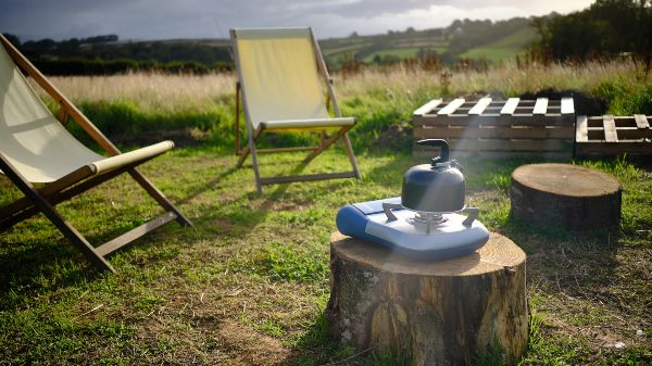 camping stove and kettle with chairs