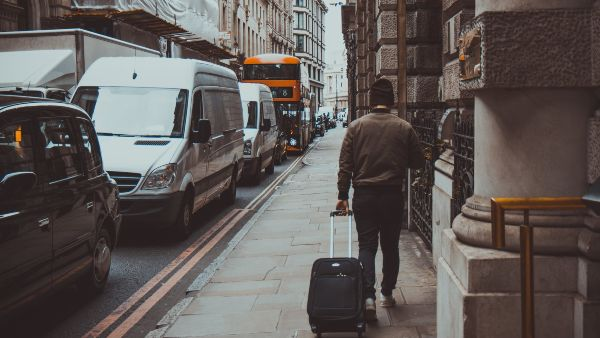 man walking down a london street with a small case