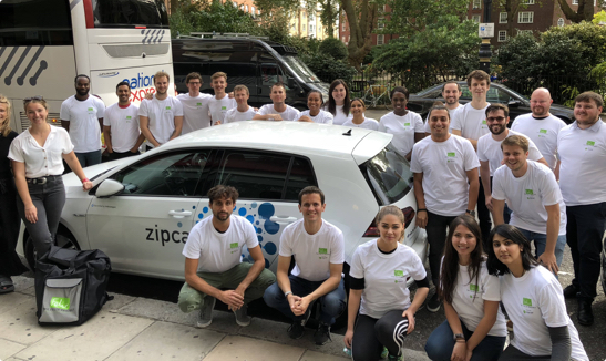 group of smiling employees in white shirts around a Flex zipcar
