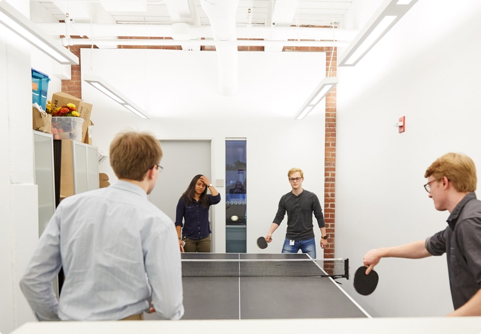 Four people playing ping pong